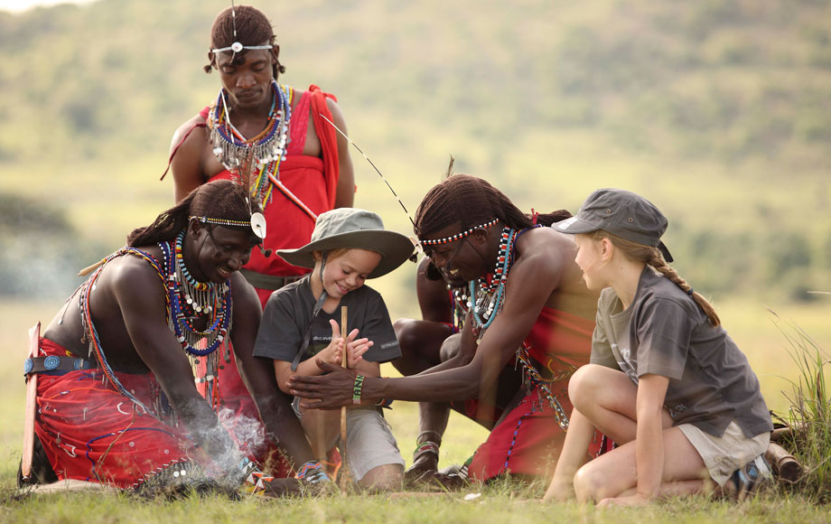 Masai warriors teaching kids how to start a fire