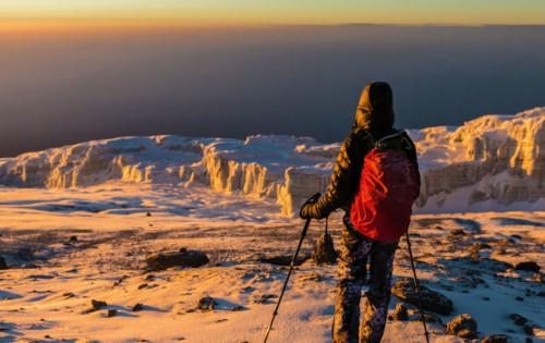 Trekker at the top of Mount Kilimanjaro